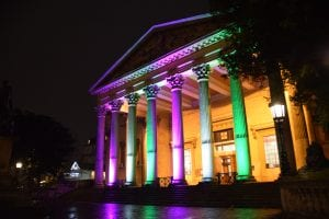 The Victoria Rooms lit up in suffragette colours