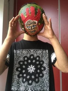 A teenager holds a mask he has made in front of his face