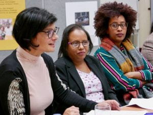 Three women sit at a table, one is addressing the audience