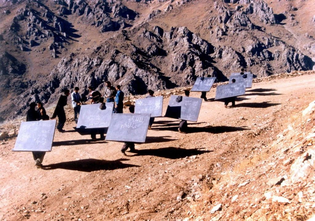 Men carrying large blackboards on their backs up a mountain path