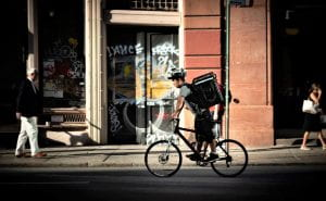 Man rides a bicycle carrying a large bag containing a food delivery