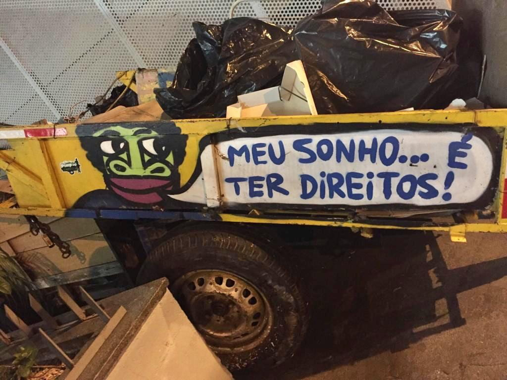 A cart on the street filled with rubbish, with painting and slogan on the side