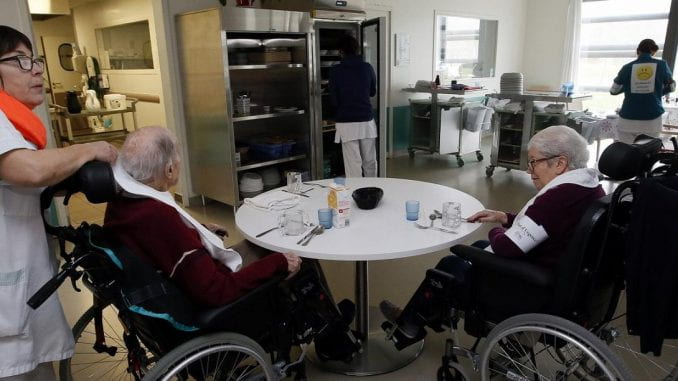 Two elderly people in wheelchairs sit at a table waiting to be served