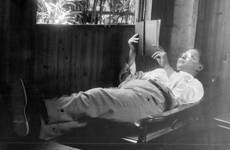 Sun Ke reading on a wooden chaise longue