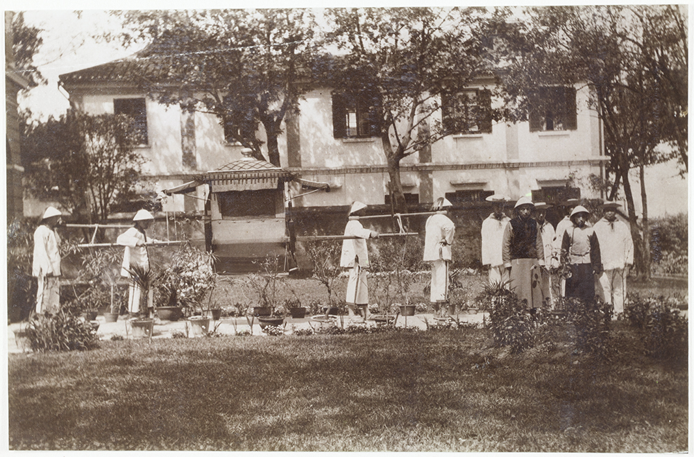 4. Kiukiang, 1904. 'My official chair and bearers with official servants waiting in the garden for me to go on a round of official calls. The building at the back is the Chinese Post Office of which I am Postmaster'.