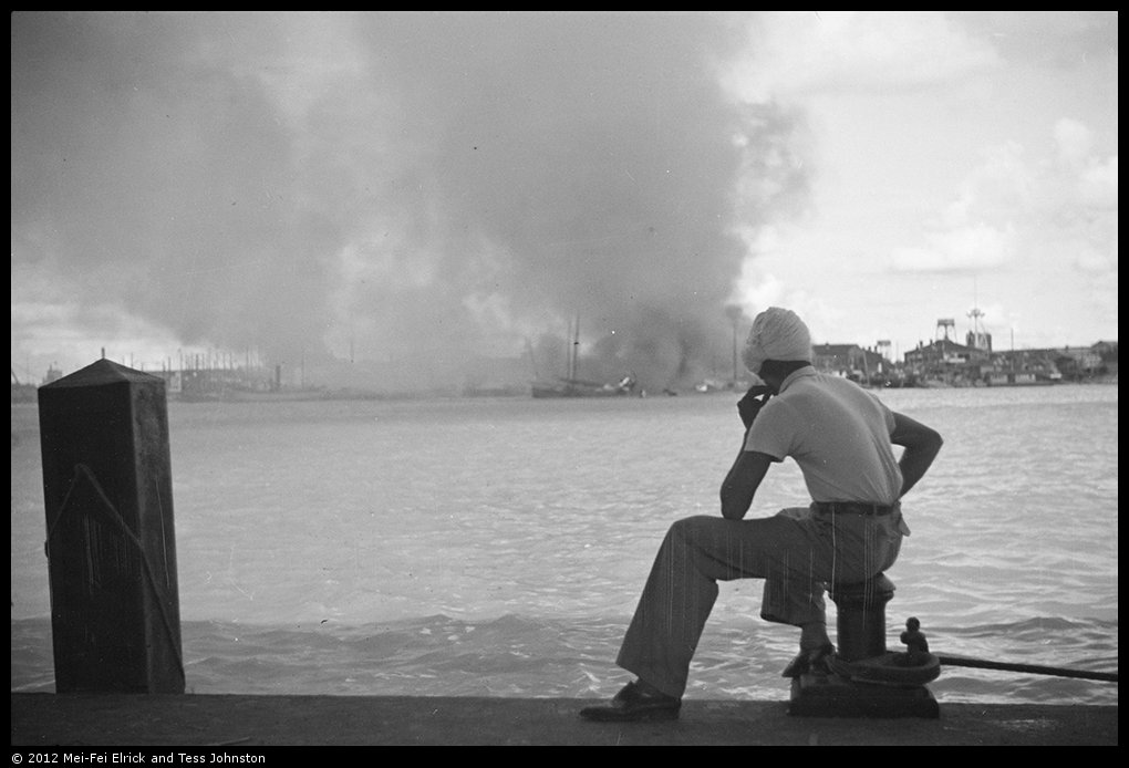 Sikh man looking over Huangputowards fires in Pudong, Shanghai, Rosholt Collection, Ro-n0382.