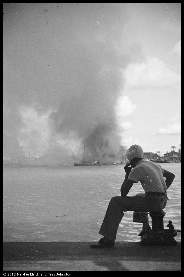 Sikh man looking over Whangpoo towards fires in Pudong, Shanghai, Rosholt Collection, Ro-n0344.