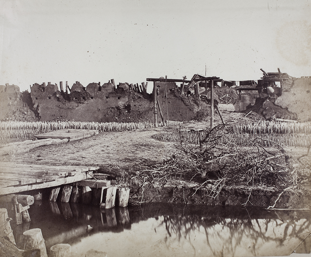 2.The Upper North Taku fort stormed by the 67th on 21 August 1860. The wooden pontoon had been laid by sappers. Ahead of it are the fixed defences of iron and wooden stakes 'thick as the pins on a pin-cushion' and beyond them, the 18 foot wide ditch which the first attackers had to swim before the drawbridge was lowered into position. Photograph by Felice Beato. GA01-038.