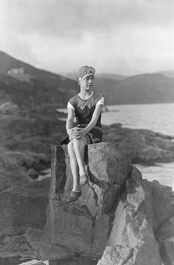 A woman in a swimsuit sitting on a rock. Photograph by Fu Bingchang. Fu Bingchang Collection, Fu-n597 © 2007 C. H. Foo and Y. W. Foo.