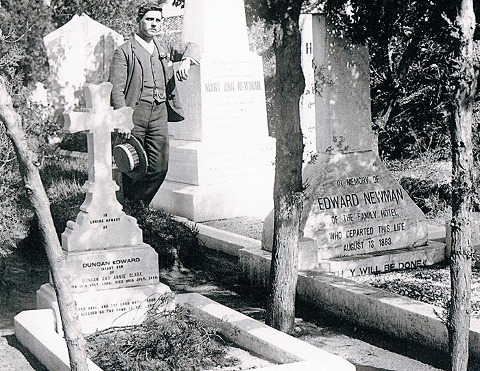 Frank Newman beside the grave stones of Mary Ann Newman and Edward Newman. Image courtesy of Duncan Clark.