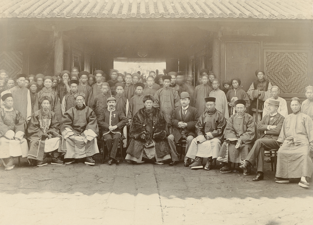 The caption is problematic. In Carey's writing, on the back of the photograph, it reads, omitting the phrase in brackets, 'Group of [Chinese and] Customs officers at the official opening of the Semao Customs house'. On the front, written on the mount, presumably by the RGS, is the same caption but with the addition of the part in brackets. This would seem more accurate as, plainly, this is not the staff of the Customs house, save for Carl, in bowler, and Carey, in boater. In uniform on the left is the French Consul, Pierre-Rémi Bons d'Anty. The official in the centre may be the Daotai with other local officials and staff in the local bureaucracy. © Royal Geographical Society (with IBG).