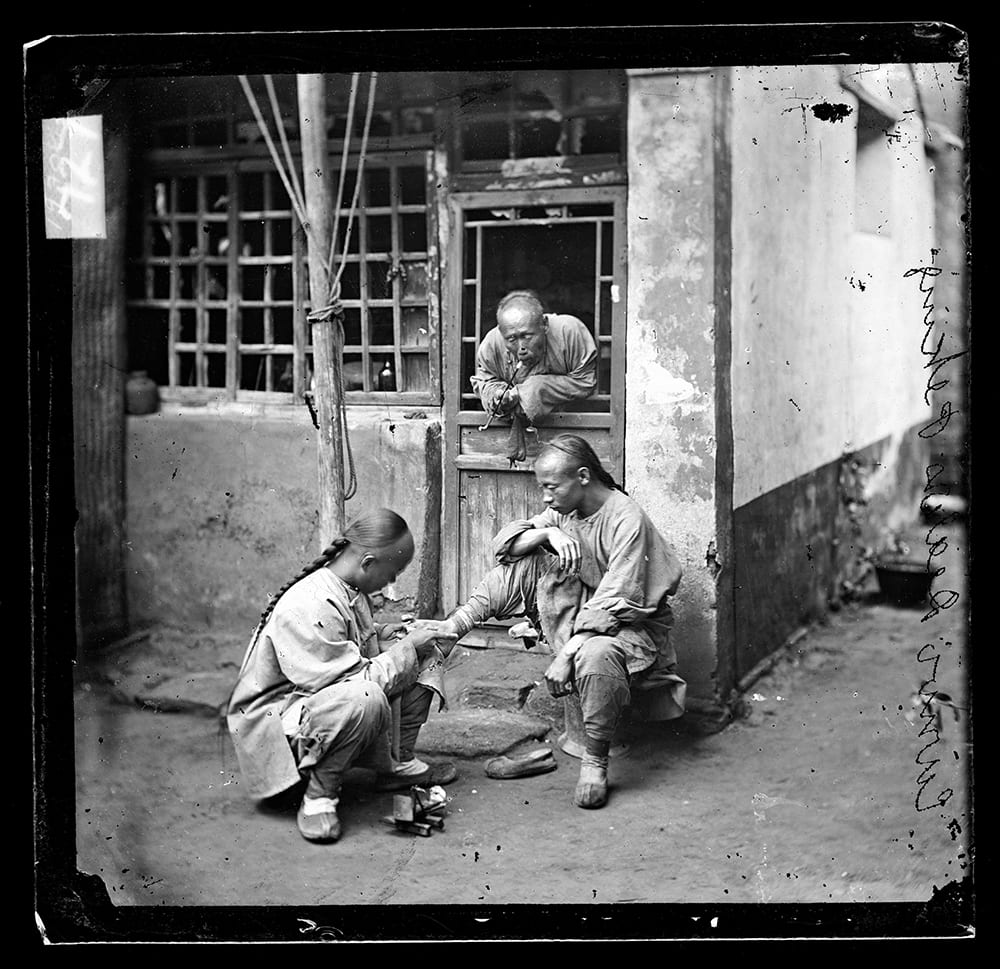 Fig. 5. One of a group of four 'medical men', the photograph shows a Pekingese chiropodist tending one patient, whilst another waits his turn. It appears in Illustrations of China, IV, plate 11. Photograph by John Thomson, negative no. 727. Credit: Wellcome Collection. CC.BY