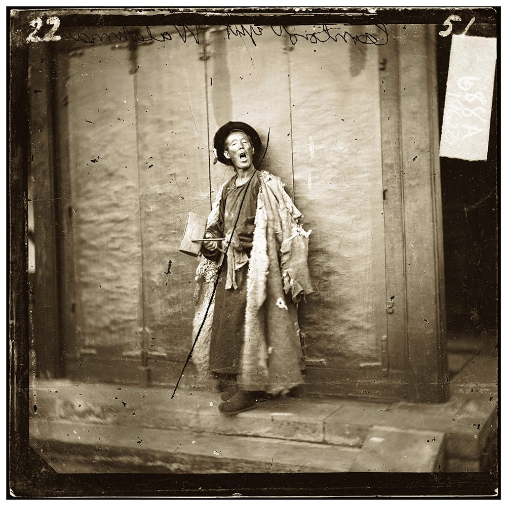 Fig. 6. Listed as 'one of the city guard, Peking', the photograph shows a night-watchman with his wooden board, used to sound that all was well: 'wrapped in his sheep-skin coat and in an under-clothing of rags, he lay through cold nights on the stone steps of the outer gateway and only roused himself to answer the call of his fellow-watchmen near at hand', Illustrations of China, IV, plate 22. Photograph by John Thomson, negative no. 688a. Credit: Wellcome Collection. CC.BY.
