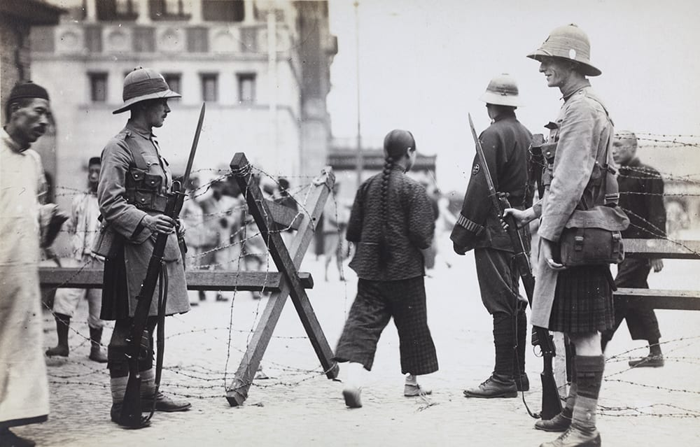 Shanghai Volunteer Corps at a street barricade. HPC ref AL-s12. Comprising a multi-national militia (including Chinese volunteers) under the control of British soldiers, the SVC, which was mobilised, for this emergency, in September 1924, represents the ambiguities of British military service on China's sovereign territory.