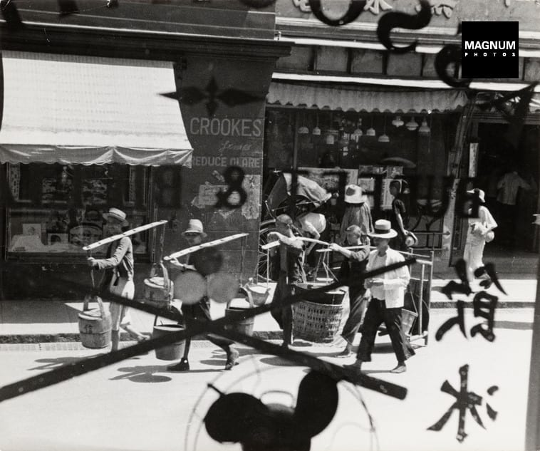 Robert Capa, CHINA. Hankou. July-September, 1938. Men, seen through a window, walking through street after the air battle between Japanese and Chinese fighter planes. © Robert Capa © International Center of Photography/Magnum Photos