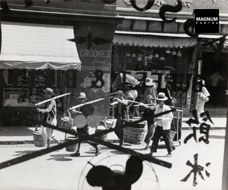 Robert Capa, CHINA. Hankou. July-September, 1938. Men, seen through a window, walking through street after the air battle between Japanese and Chinese fighter planes. © Robert Capa © International Center of Photography/Magnum Photos
