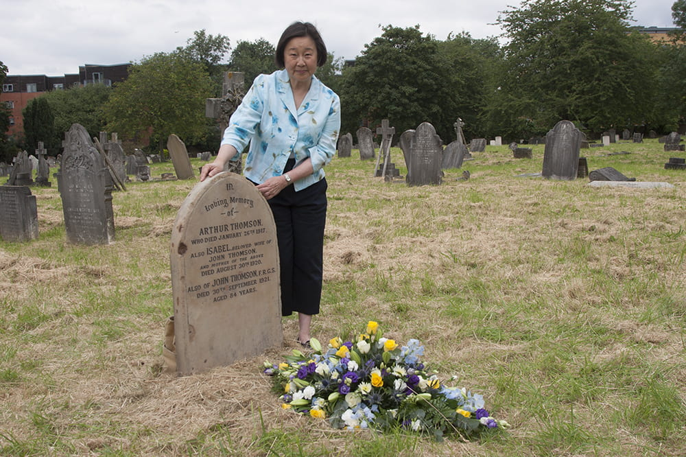 Betty Yao MBE beside John Thomson's restored grave, Streatham Cemetery, Tooting, London, 13 July 2019. Photograph by Jamie Carstairs.