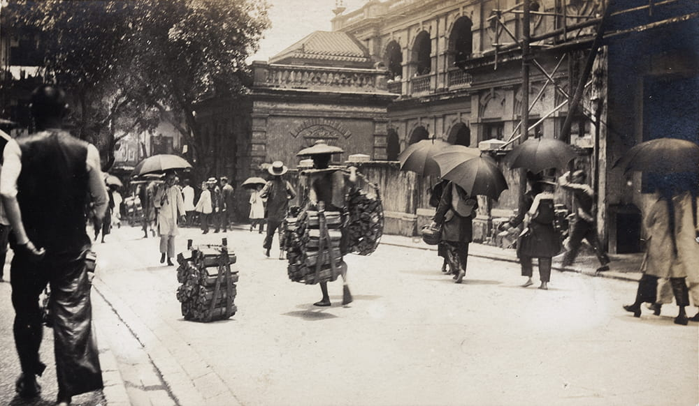 Porters carrying wood, and women with umbrellas, Hong Kong. Historical Photographs of China ref: Mi01-033.
