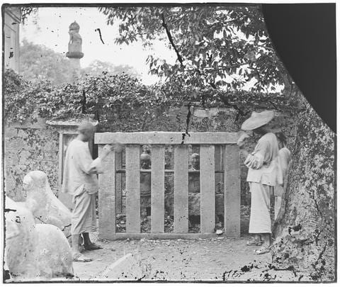 """Photograph by C.F. Moore. Two men posed, seemingly throwing stones at iron figures, at Yue Fei Temple (Yuewang Temple 岳王廟), West Lake, Hangzhou. This photograph (negative ref no: J-00496) is listed in Moore's 'China in the Time of General Gordon' lecture notebook: """"13. Iron figures in stone cages, being the conspirators who compassed the death of Yoh Fei, his son and family."""" See Ar01-016 (note the sculpture on a column in both images)."""
