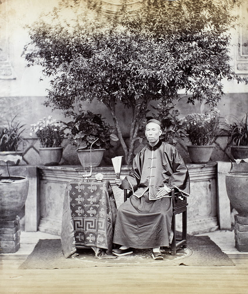 A portrait of Hopchun, c.1869, in which a tea plant is central in a symmetric composition. Photograph attributed toLai Fong (Afong Studio), as suggested by the number written in pencil on the album page (30). See the Lai Fong (Afong Studio) number lists in'History of Photography in China, Chinese Photographers 1844-1879'by Terry Bennett (Quaritch 2013), page 312. HPC ref: Fr01-046.