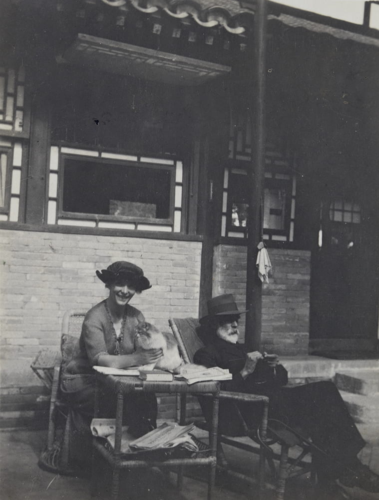 Guy, knitting at Balizhuang, late autumn 1921. Books are on the table and Ella is holding their cat Carpentier. HPC ref: EH01-343.