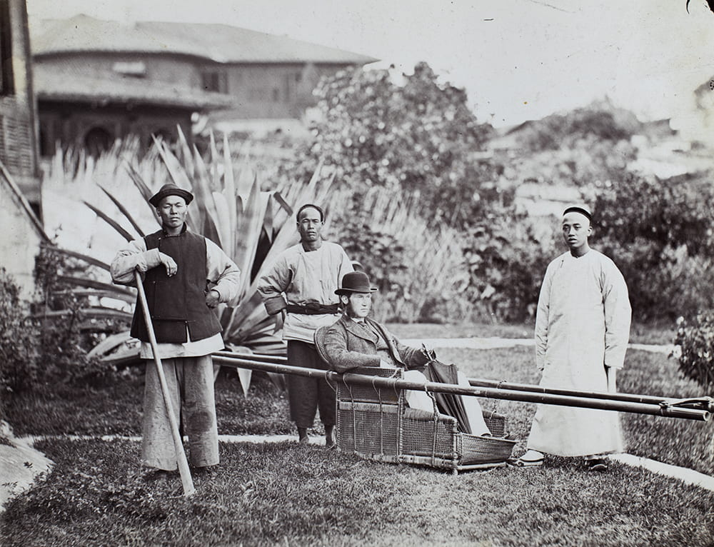 John Gurney Fry is depicted, somewhat idiosyncratically, with bowler and umbrella, in a sedan chair parked in the garden of 'The Old Bungalow', with his gardener, chair bearer and a house servant, Fuzhou, c1869-1870. HPC ref: Fr01-014.
