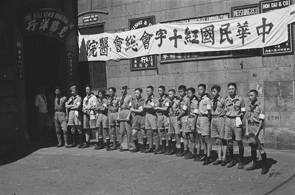 Boy scouts outside Shanghai Stock Brokerage Corporation office (serving as a red Cross hospital), Shanghai. Photograph by Malcolm Rosholt. HPC ref: Ro-n0156.