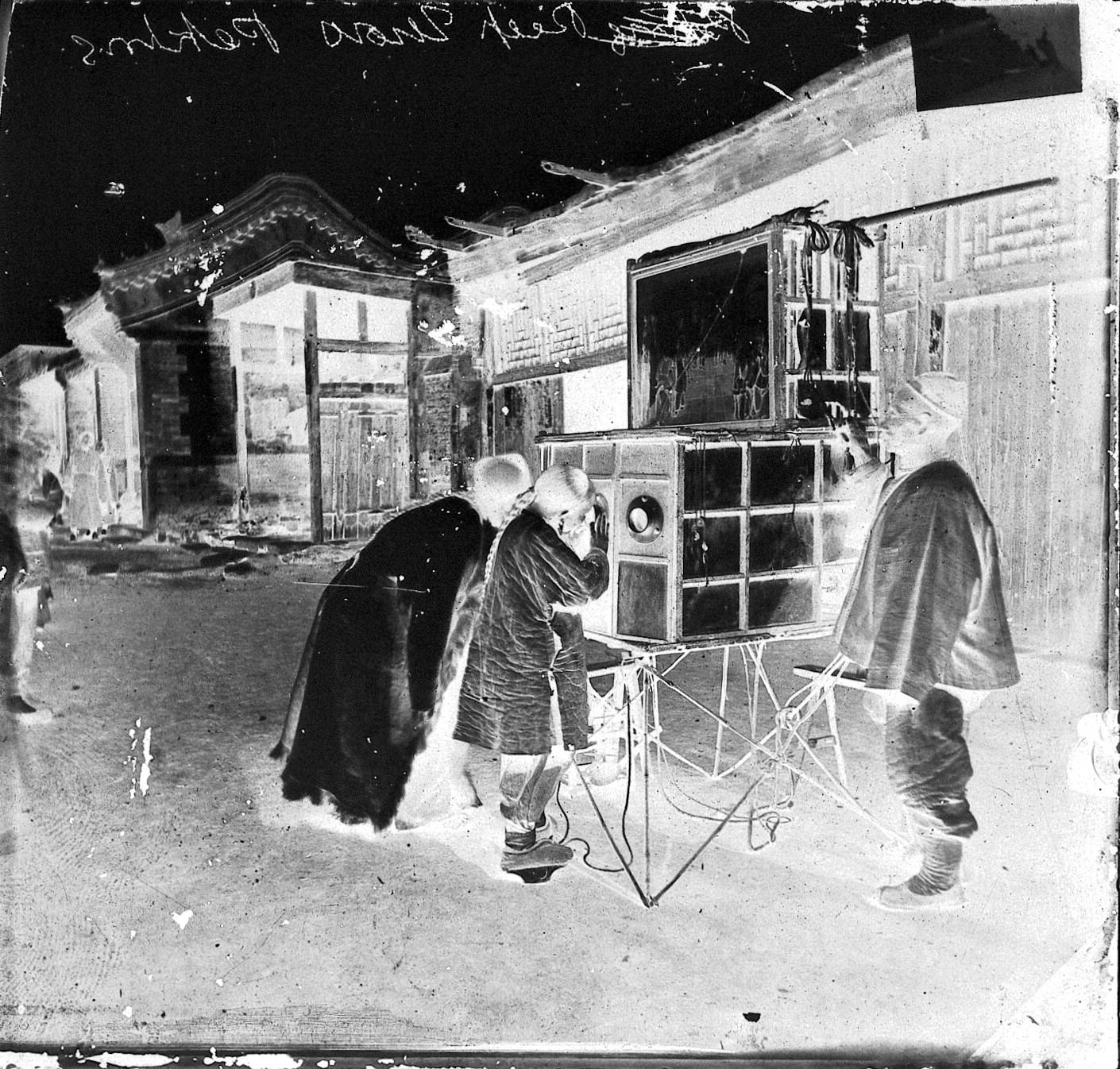 Looking at a peep show in the street, Beijing, c.1870. Photograph by John Thomson. The exhibition prints were made from glass negatives digitised by the Wellcome Collection. Credit: Wellcome Collection. Attribution 4.0 International (CC BY 4.0).