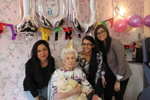 Students celebrating Ada's 100th birthday in local care home