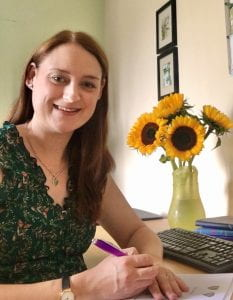 The author sits at her desk, smiling at the camera, about to sign a contract.