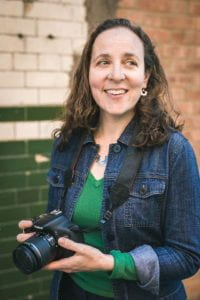 Amelia stands outdoors against a cream and green brick wall. She holds a camera and smiles.