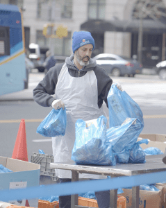 Greg Silverman stands behind a table on the pavement, organising blue plastic bags full of food.