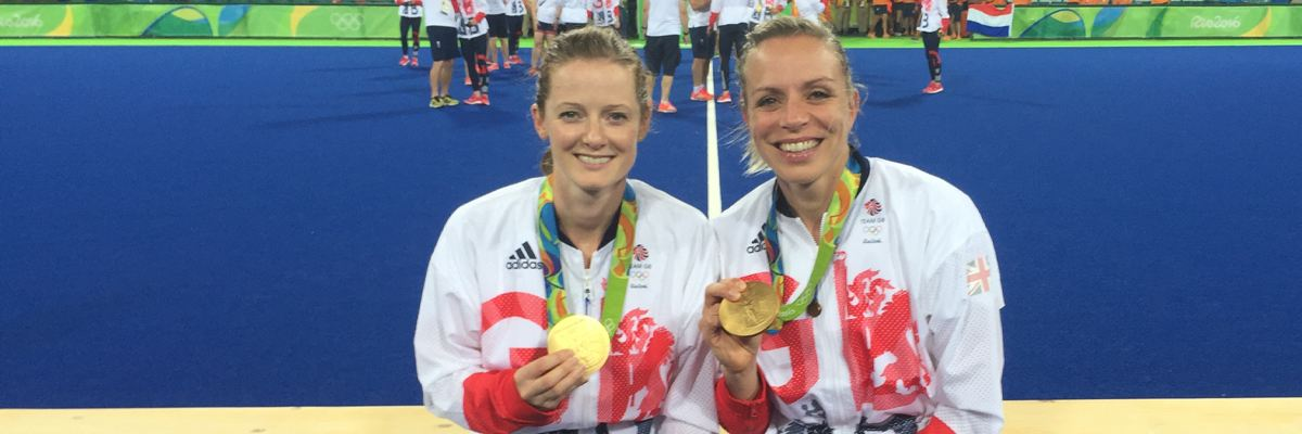 Helen and Kate sit next to each other on the podium showing their medals and smiling at the camera.