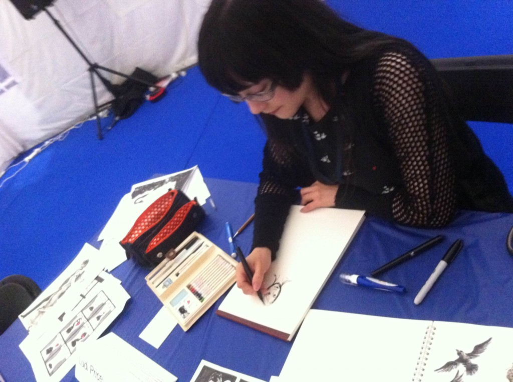Me drawing in the Loncon 3 fan activity tent.