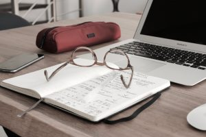 notebook and glasses in front of comptuer
