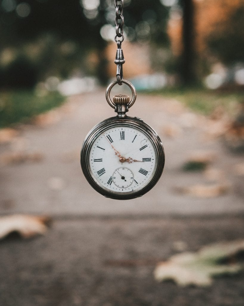 Dangling pocket watch above a path with leaves to the side