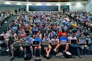 Students at University Missouri School of Journalism, with laptops open in a lecture hall.