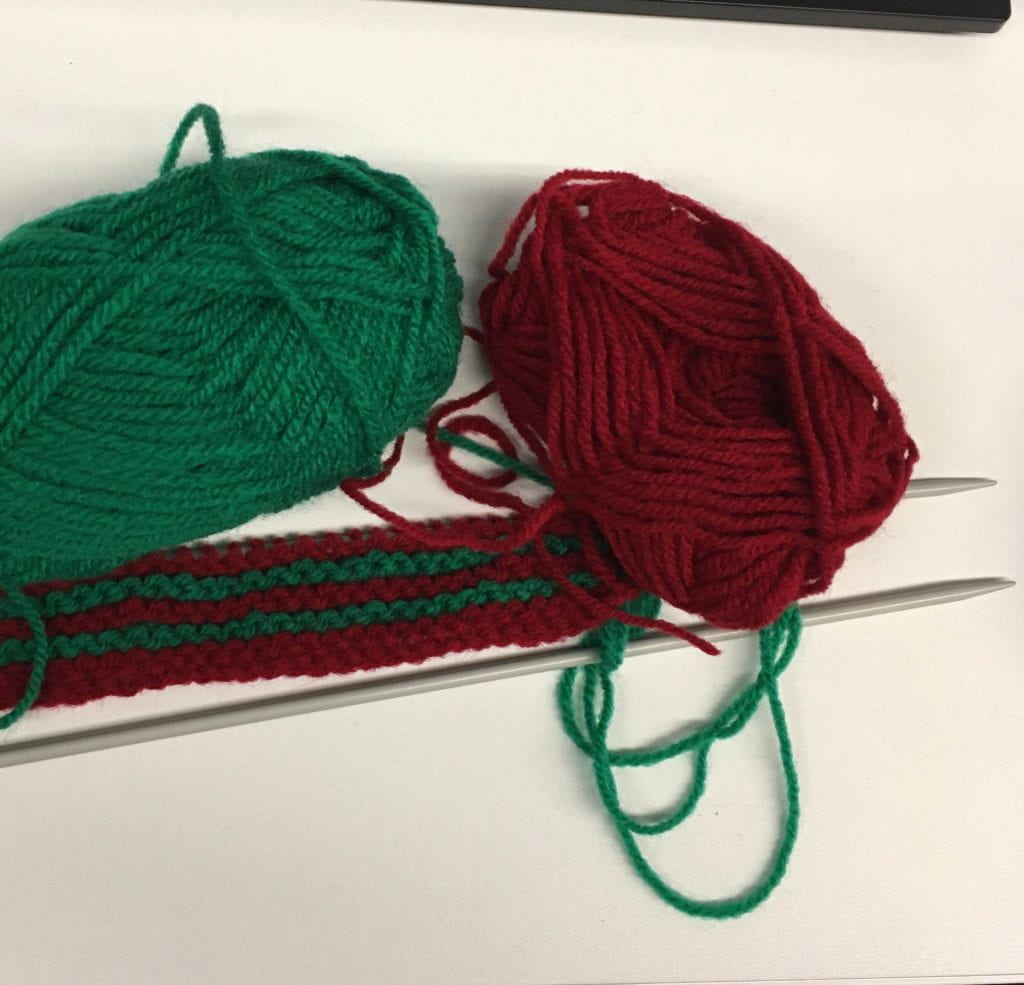 A short piece of knitting, two needles. Balls of red and green wool