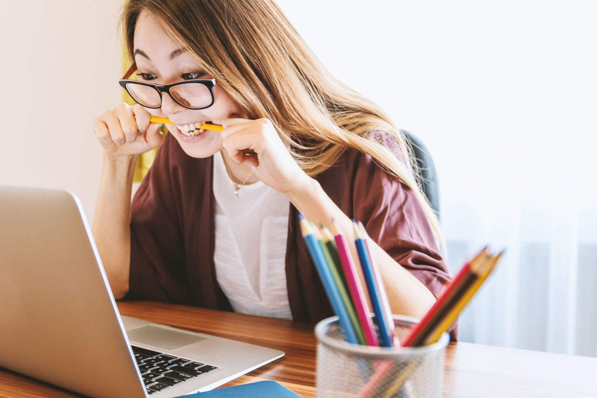 Woman biting pencil while sitting in front of computer