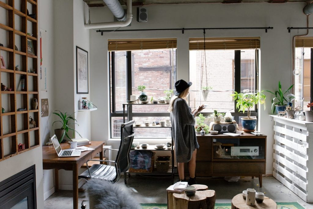 young woman in work studio alone next to window