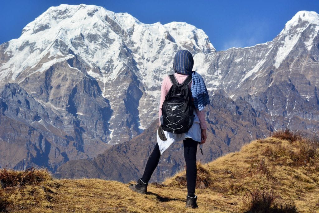 A woman trekker stands at the top of a hill