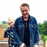 Photo of Edwyn and Grace in front of a field in the countryside. Edwyn stands in front wearing a denim jacket and black top. Grace stands behind him peering around his right shoulder and looking into the camera.