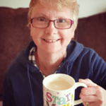 """Jan sits on a sofa, smiling up at the camera. She is holding up a mug of tea in her left hand. The mug says the words """"Star Mum"""""""