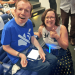 Lee sits in a chair with his iPad on his knee. He is smiling at the camera. Abi is crouched beside him, smiling. Abi is giving a thumbs up of excitement.