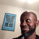 """Graeme is looking off to the left of the picture, smiling. A posted on the wall behind him, says, in clear lettering """"clear your head""""."""