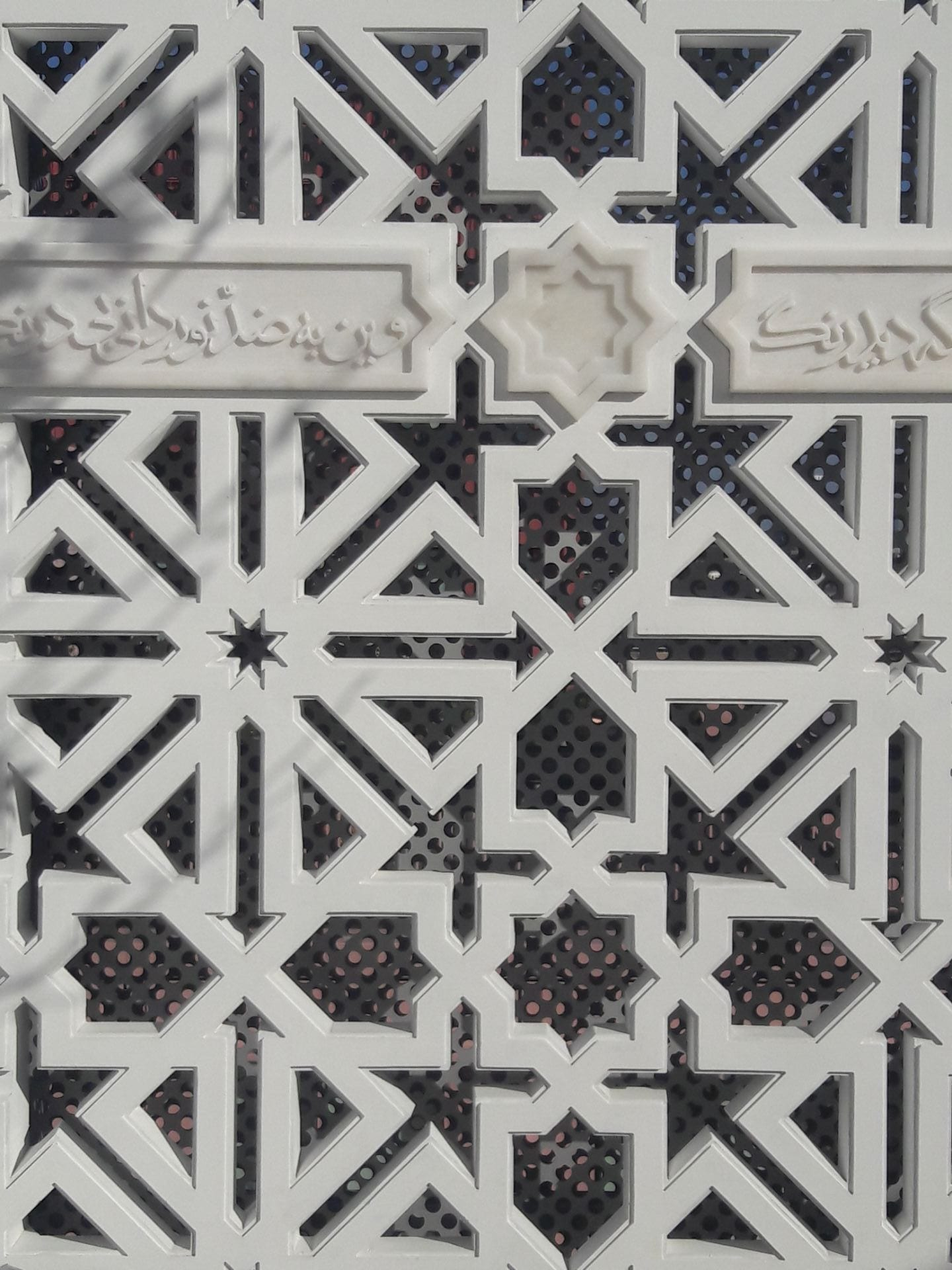 Detail from the white trellis in the Garden of Light with 8 pointed star design and extract from the Qu'ran.