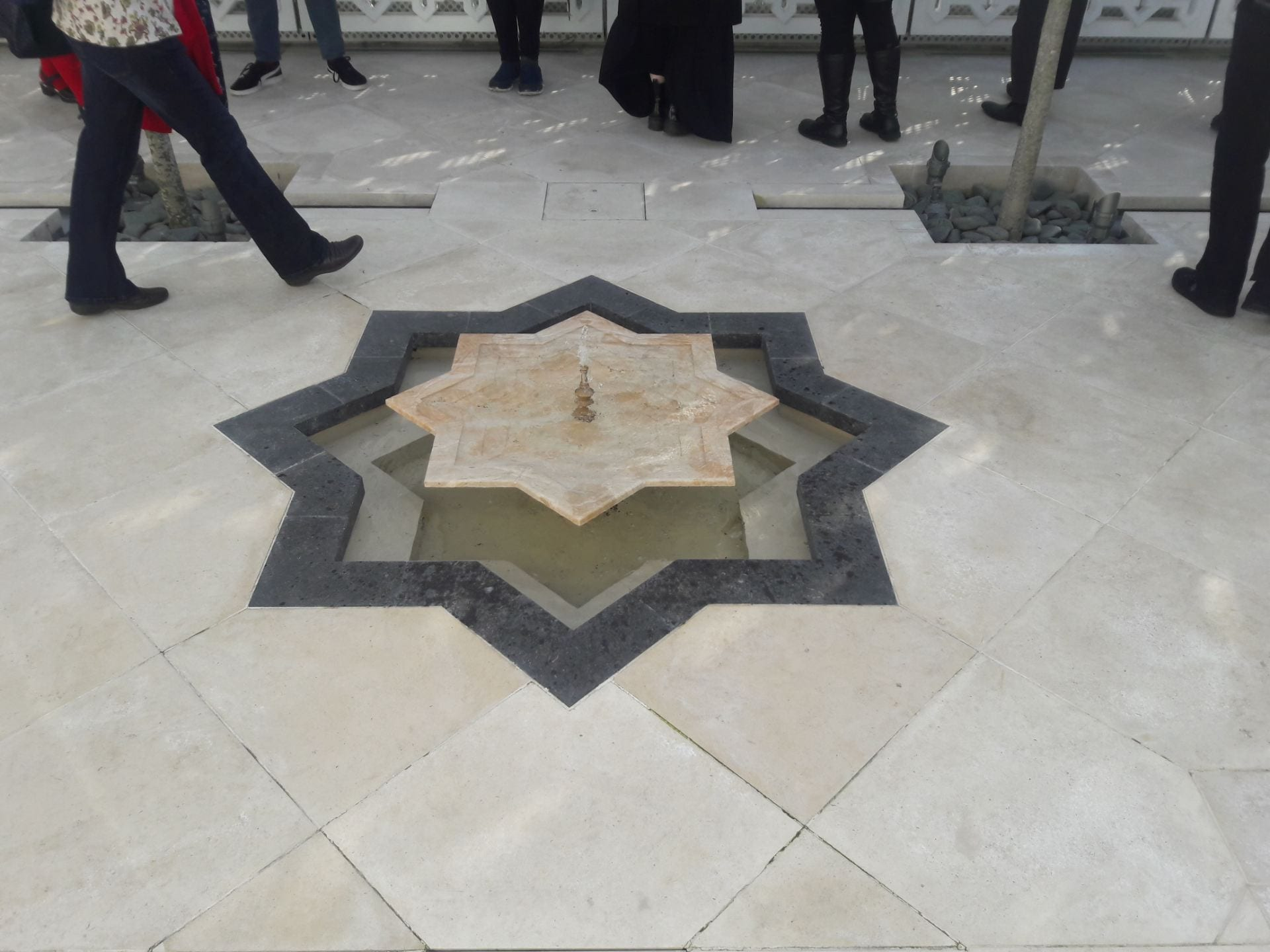 A small fountain in one of the Aga Khan Terrace gardens. The fountain is cut into the cream paving slabs and is shaped as an 8 pointed star.