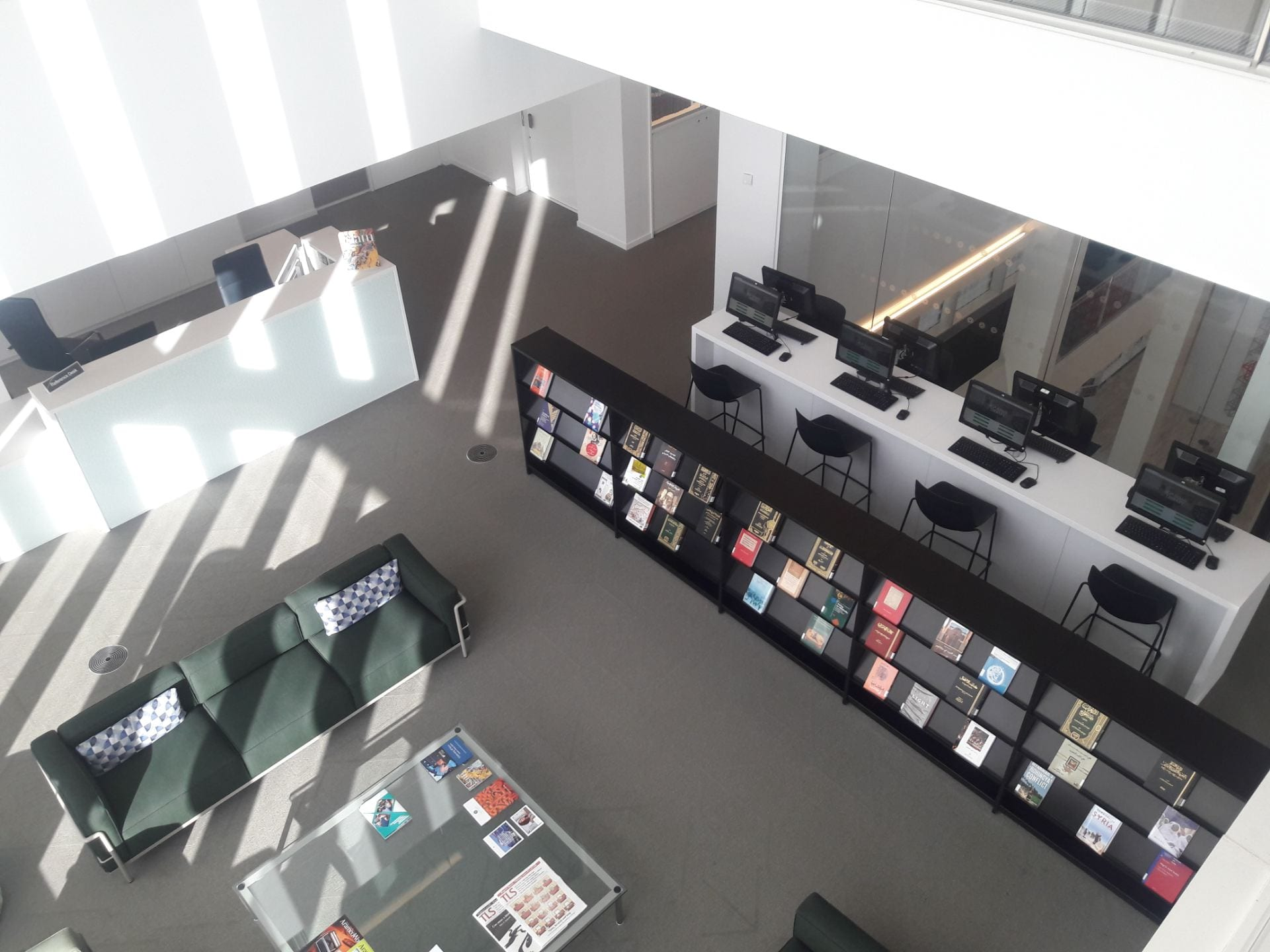 The entrance area of the Aga Khan Library taken from the floor above. The Library Help desk, soft furnishing, coffee table, journal shelves and catalogues and stools can be seen. There is light streaming in.