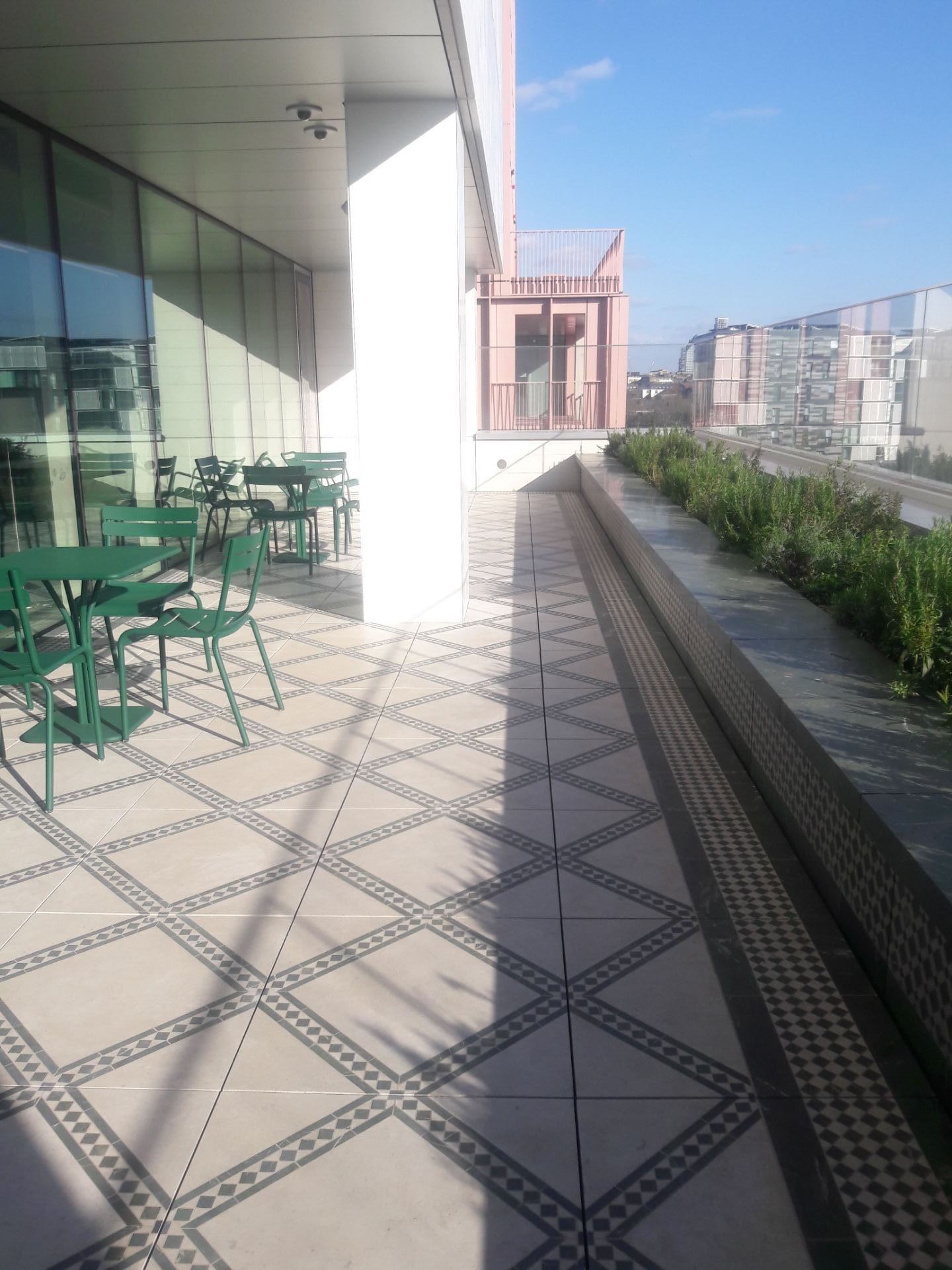 The Terrace of learning, a semi covered terrace in the sunlight. Floor tiles with geometric pattern in the North African style. Green garden tables and chairs sit close to the full length windows. Green evergreen herbs can be seen in the planter.