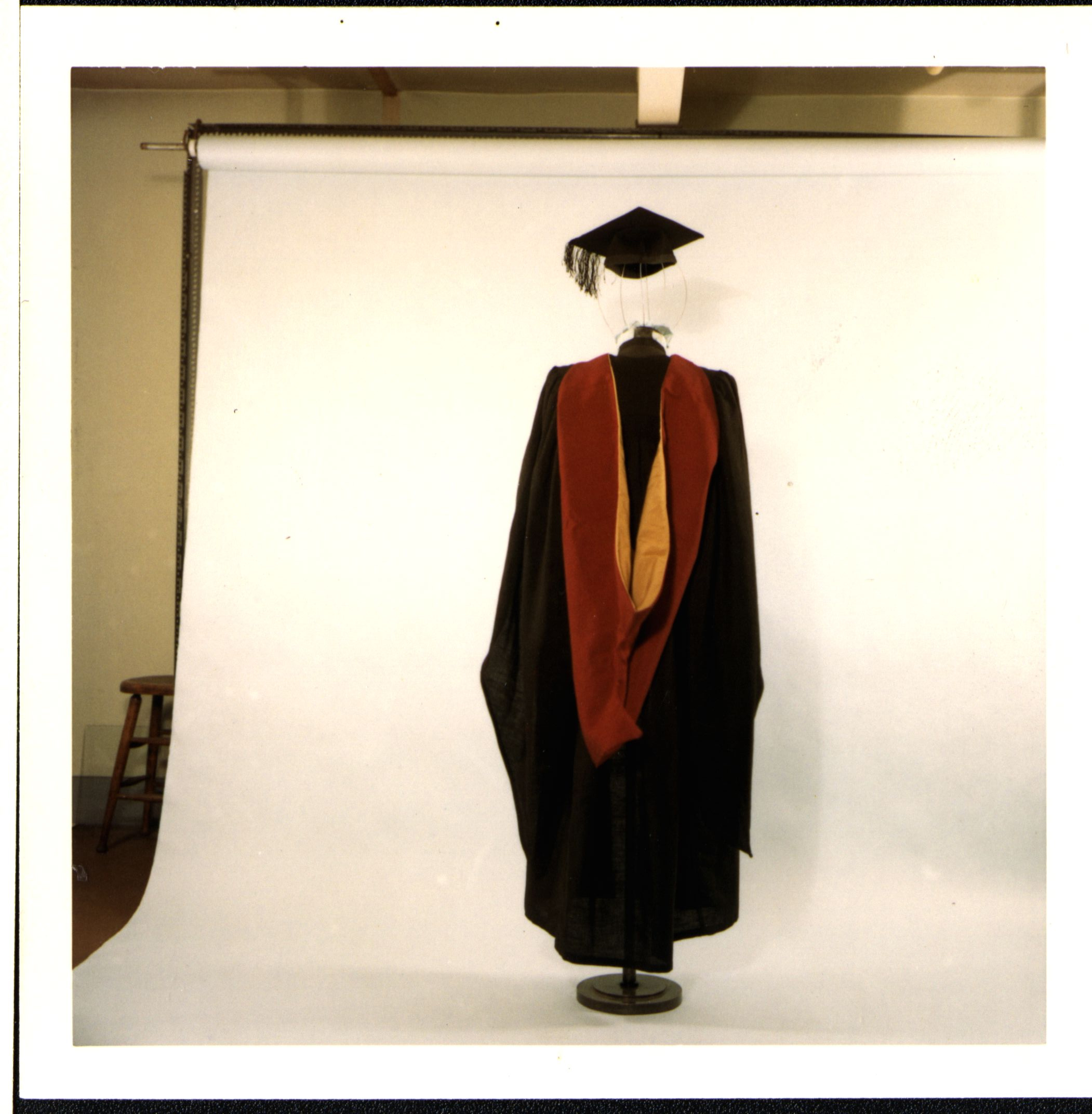 City Bachelor graduation robes black robe with red and yellow hood, back view.